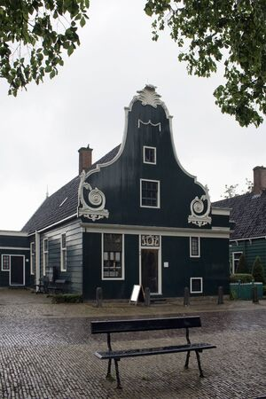 View of old, historical, wooden house and a bench in Zaanse Schans neighborhood in the Dutch town of Zaandam, near Amsterdam. It is a rainy summer day.