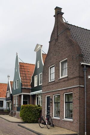 View of historical and traditional houses, bicycles in Volendam. It is a Dutch town, northeast of Amsterdam. It's known for its colorful wooden houses and the old fishing boats.