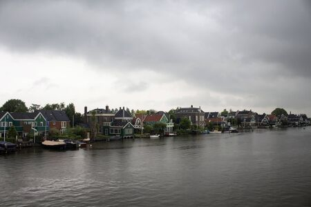 View of small town called Zaanse Schans, neighborhood in the Dutch town of Zaandam, near Amsterdam. The town is famous for historic windmills and distinctive green wooden houses.