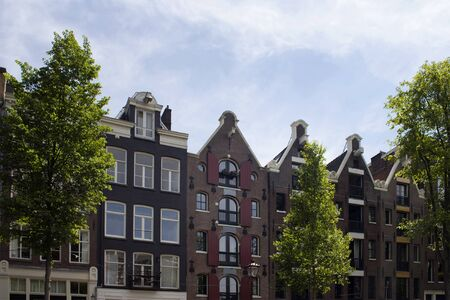 View of historical, traditional and typical buildings showing Dutch architectural style and trees in Amsterdam. It is a sunny summer day with blue sky.