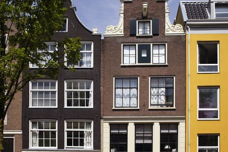 View of historical, traditional and typical buildings showing Dutch architectural style and a tree in Amsterdam. It is a sunny summer day. Stock fotó