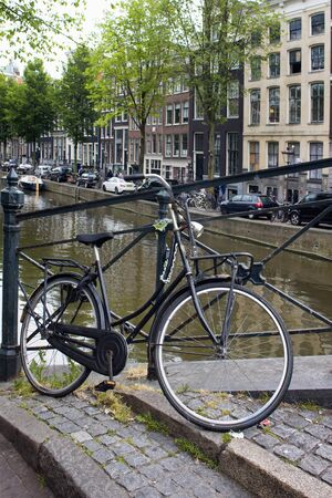 Close up view of parked bicycle in Amsterdam. Canal, trees, cars and historical and traditional buildings are in the background. It is a summer day Stock fotó