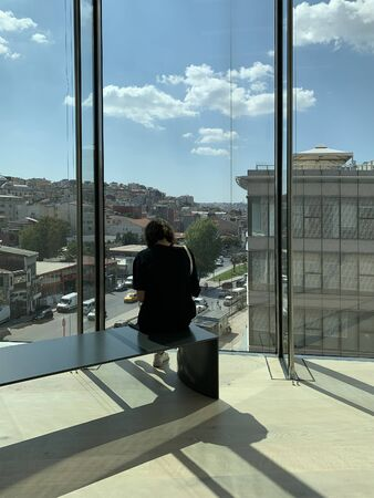 View of a woman sitting on a bench at newly opened contemporary art museum in Istanbul. Dolapdere area of Istanbul and cloudy blue sky are in the background.