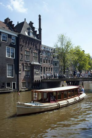 View of canal cruise tour boat passing by Armbrug bridge in Amsterdam. Historical, traditional and typical buildings and people are in the background. It is a sunny summer day. 報道画像