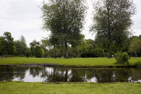 View of people hanging out, trees, grass field, pond at Vondelpark in Amsterdam. It is a public urban park of 47 hectares. It is a summer day.