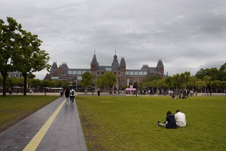 View of people at hanging out at Museum Quarter (square) in Amsterdam. Rijksmuseum is in the view. It is a summer day with cloudy sky. 報道画像
