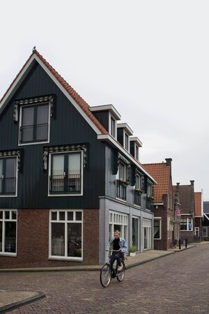 View of woman riding bicycle in blurry motion and historical and traditional houses in Volendam. It is a Dutch town, northeast of Amsterdam.
