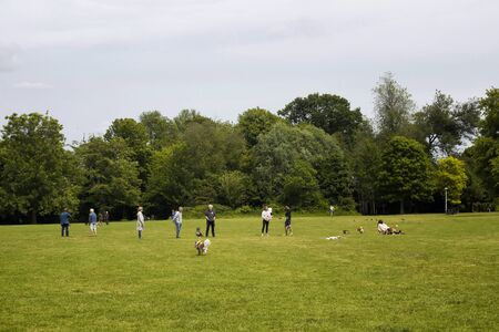 View of people hanging out on grass field with their dogs, trees at Vondelpark in Amsterdam. It is a public urban park of 47 hectares. It is a summer day.