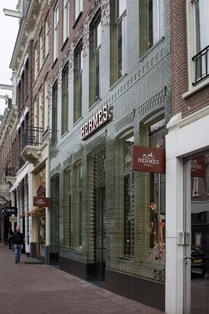 View of facade (made with glass bricks) of French fashion goods manufacturers store on on luxury shopping street named Pieter Corneliszoon Hooft in Amsterdam. It is a summer day.
