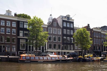 View of parked canal cruise tour boats, trees and historical, traditional and typical buildings showing Dutch architectural style in Amsterdam. It is a sunny summer day.