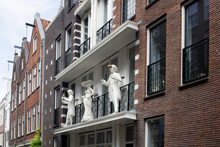 View of three statues at the balcony of a traditional building in neighborhood called Jordaan in Amsterdam. The image shows Dutch architecture style and lifestyle. 報道画像