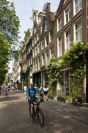 View of people walking and riding bicycles on street in Amsterdam. Historical, traditional and typical buildings are in the view. It is a sunny summer day.
