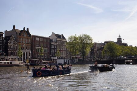 View of people riding open boats in Amstel river doing canal cruise tours. Historical, traditional and typical buildings are in the background. It is a sunny summer day with clear blue sky. 報道画像