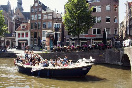 View of people riding a boat on canal doing a cruise tour in front of 13th-century The Oude Church in Amsterdam. Many people hang out on street. It is a sunny summer day. 報道画像