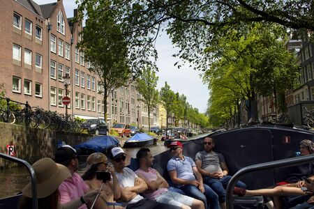 View of people on canal cruise boat tour in Amsterdam. Historical, traditional and typical buildings and trees are in the background. It is a sunny summer day.