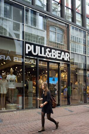 View of woman walking in blurry motion by Spanish clothing and accessories retail brands store on Kalverstraat street in Amsterdam.