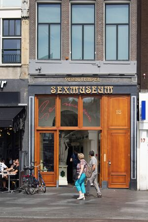 View of a couple passing by Sex Museum in Amsterdam. It is a sunny summer day. 報道画像