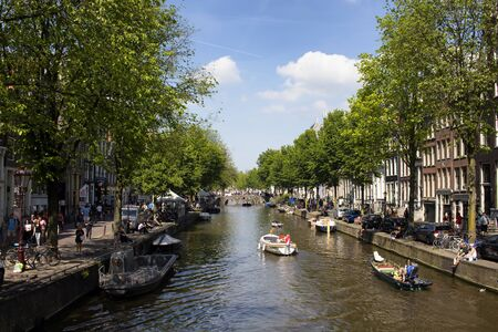 View of people riding small boats on canal doing a cruise tour in Amsterdam. Cloudy blue sky and trees are also in the view. It is a sunny summer day.
