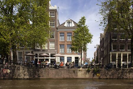 View of people hanging out by canal at a cafe, trees, historical and traditional buildings showing Dutch architecture style in Amsterdam. It is sunny summer day. 報道画像