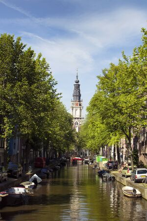 View of Zuiderkerk church, canal, trees and parked boats with blue sky background in Amsterdam. It is a sunny summer day. 報道画像