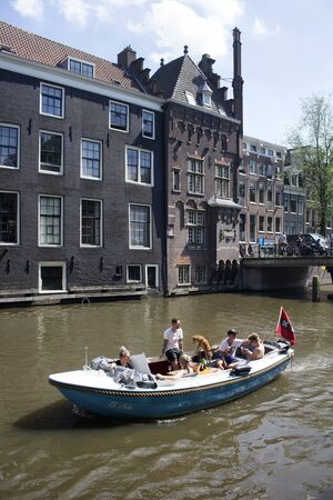 View of young people riding a small, blue, open boat in canal doing a tour at Armbrug bridge area in Amsterdam. Historical, traditional buildings are in the background.