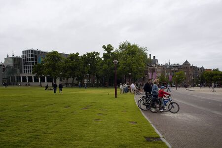 View of people at hanging out and a family riding bicycles at Museum Quarter (square) in Amsterdam. It is a summer day with cloudy sky. 報道画像