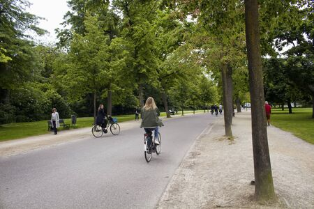 View of people riding bicycles and walking, trees and road at Vondelpark in Amsterdam. It is a public urban park of 47 hectares. It is a summer day.