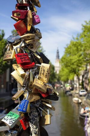 Close up view of wishlove locks (lovers padlocks) with canal, trees and Zuiderkerk church in the background in Amsterdam. It is a sunny summer day. 報道画像