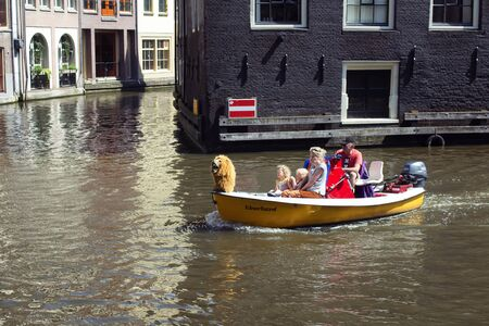 Close up view of a family riding a small, yellow, open boat in canal doing a tour at Armbrug bridge area in Amsterdam. It is a sunny summer day. 報道画像