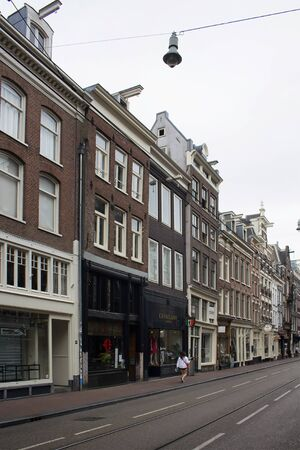View of woman walking on one of the shopping streets in Amsterdam. It is a summer day with cloudy sky.