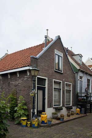 View of historical and traditional houses, plants in Volendam. It is a Dutch town, northeast of Amsterdam. It's known for its colorful wooden houses and the old fishing boats.