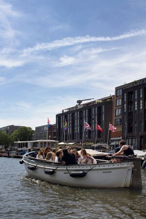 View of group of people taking a canal cruise tour in Amsterdam. Modern buildings and clear blue sky are in the background. It is a sunny summer day.