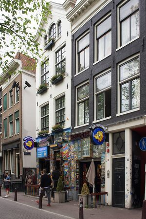 View of one of the weed cafe chains and people walking on street in Amsterdam. Traditional and typical buildings reflecting Dutch architectural style are also in the view.