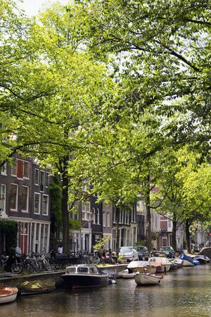 View of man riding small, wooden boat on canal, many parked boats, bicycles, trees and historical, traditional buildings showing Dutch architectural style in Amsterdam. It is a sunny summer day. 報道画像