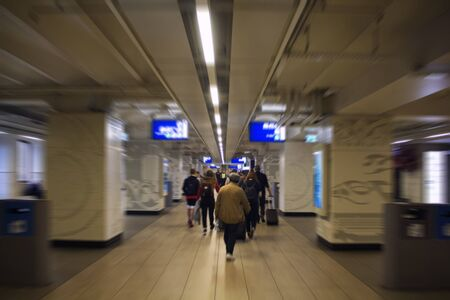 Blurry motion image of people walking at the main train station called Amsterdam Centraal. A major international railway hub, it is used by 162,000 passengers a day. Transportation concept. 報道画像