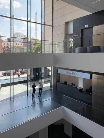 Interior view of newly opened contemporary art museum in Istanbul. Two workers and info desk area are in the view. It is a sunny autumn day. 報道画像