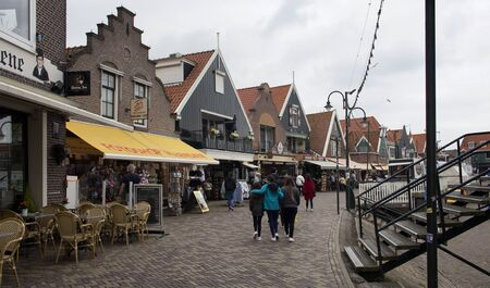 View of people walking at the pier, shops and restaurants in Volendam. It is a Dutch town, northeast of Amsterdam. It's known for its colorful wooden houses and the old fishing boats.