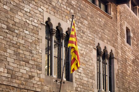 """View of Catalan flag at historical, old building in """"Ciutat Vella"""" district (Gothic Quarter) in Barcelona. It is a sunny summer day."""