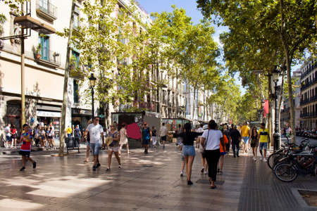 """View of people walking, traditional and historical buildings and trees on famous street called """"La Rambla"""" in Barcelona. Editorial"""