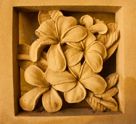 Yellow flowers made of stone. By means of carving