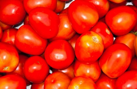 Many tomatoes. Sold in the market.