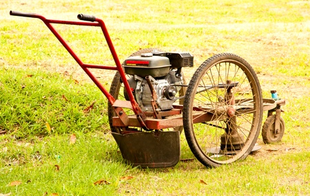 Lawn mower in action with cutting grass  on ground  photo