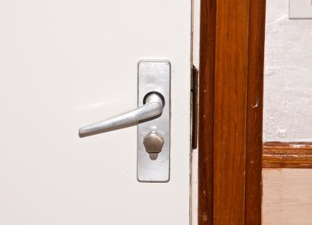 Aluminium door knob on the white door Stock Photo