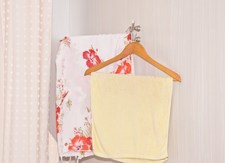 Towel draped on coat hanger in the corner of the room  photo