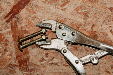 Adjustable wrench and bolt  on wood wall background photo