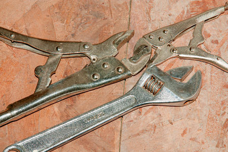 Adjustable wrench on wood wall background