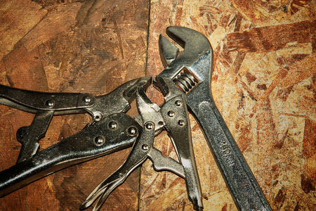 Adjustable wrench on wood wall background photo