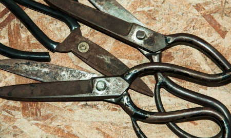 Scissors for cutting leather on wood wall Stock Photo