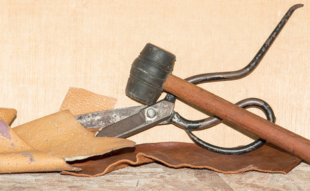 tailor seat: Scissors for cutting leather, placed on a wooden floor