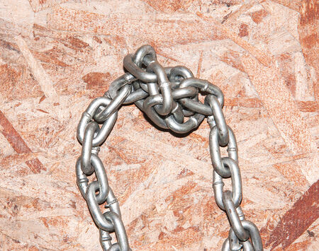 tightly: Chains are tightly bound on wooden table